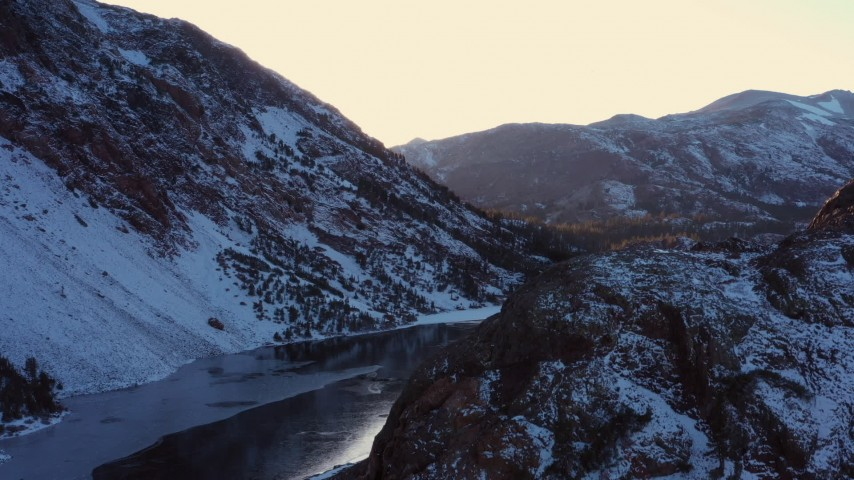 4K stock footage aerial video ascend with view of snowy Sierra Nevada Mountains by lake at sunset, Inyo National Forest, California Aerial Stock Footage | CAP_015_029