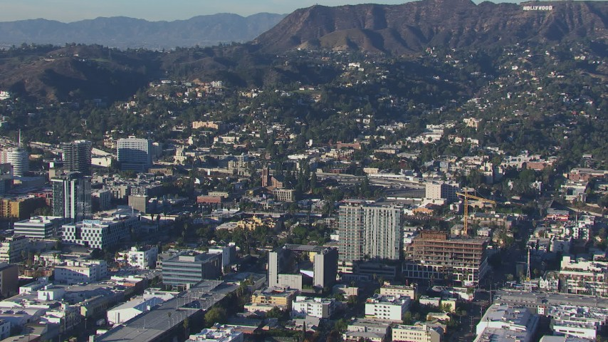 HD stock footage aerial video orbit apartment buildings and college, reveal the Hollywood Sign Hollywood, California Aerial Stock Footage | CAP_016_010