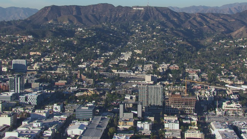 HD stock footage aerial video orbit apartment buildings and college with view of the Hollywood Sign, California Aerial Stock Footage | CAP_016_011