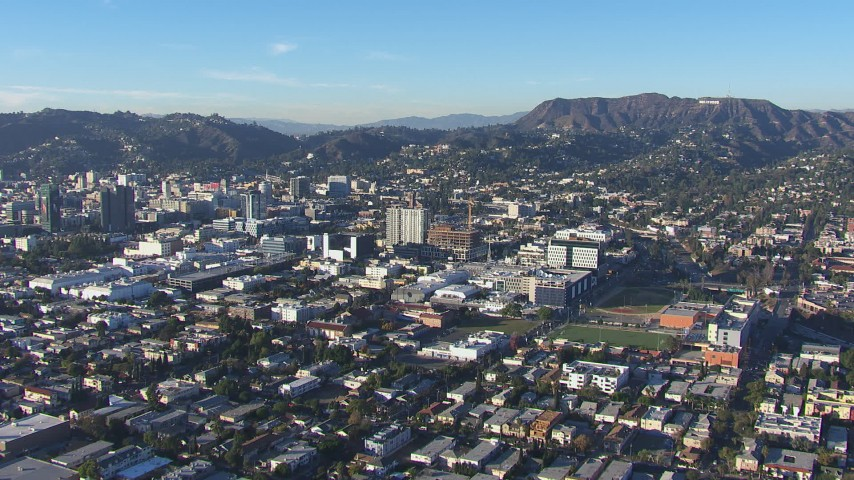 HD stock footage aerial video of flying away from Hollywood Sign and office buildings, California Aerial Stock Footage | CAP_016_026