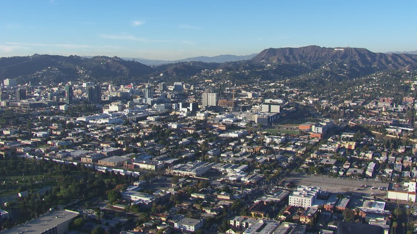 HD stock footage aerial video of a reverse view of Hollywood Sign and office buildings, California Aerial Stock Footage | CAP_016_027
