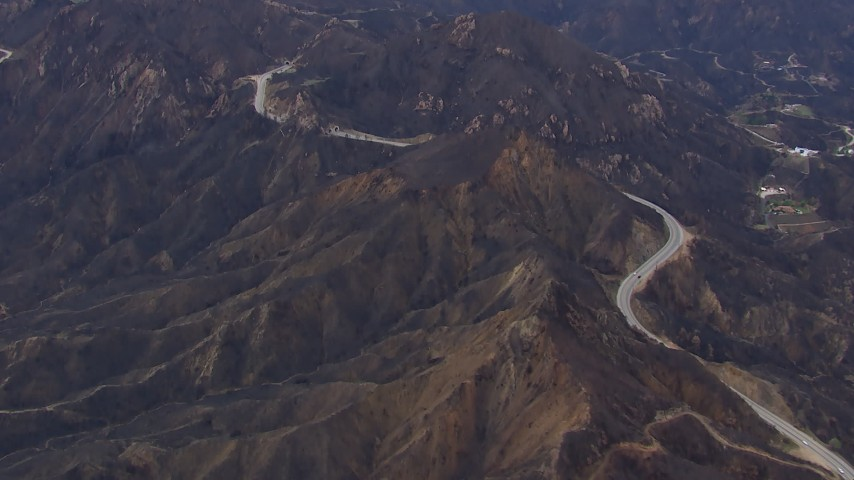 HD stock footage aerial video of flying by road by mountains scarred by fire, Malibu, California Aerial Stock Footage | CAP_018_014