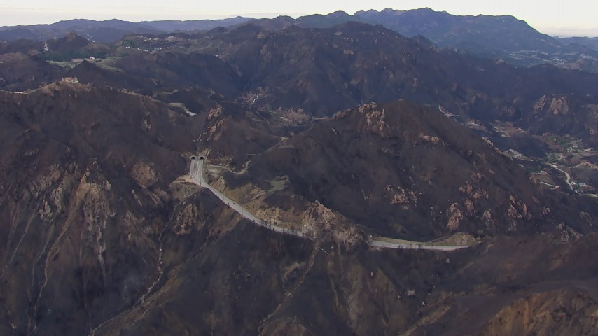 HD stock footage aerial video of flying by road and tunnels by mountains scarred by fire, Malibu, California Aerial Stock Footage | CAP_018_016