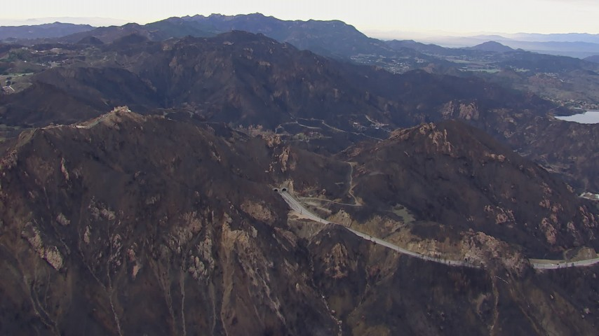 HD stock footage aerial video of passing road and tunnels by mountains scarred by fire, Malibu, California Aerial Stock Footage | CAP_018_017