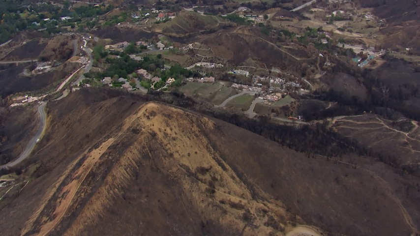 HD stock footage aerial video of flying over a mountain scarred by fire to approach destroyed homes, Malibu, California Aerial Stock Footage | CAP_018_019