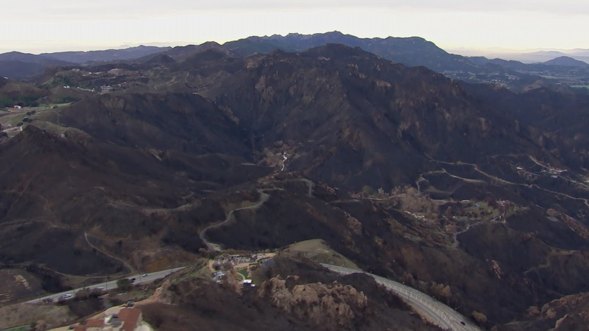 HD stock footage aerial video reverse view of hillside homes destroyed by fire by scorched mountains, Malibu, California Aerial Stock Footage | CAP_018_027
