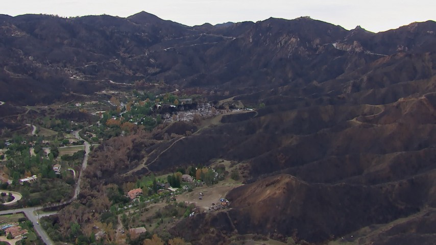 HD stock footage aerial video of approaching homes destroyed by fire by scorched mountains, Malibu, California Aerial Stock Footage | CAP_018_028