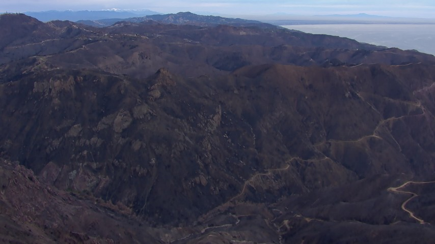 HD stock footage aerial video of flying over mountains scorched by fire, Malibu, California Aerial Stock Footage | CAP_018_039