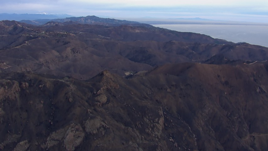 HD stock footage aerial video of approaching mountains scorched by fire, Malibu, California Aerial Stock Footage | CAP_018_040