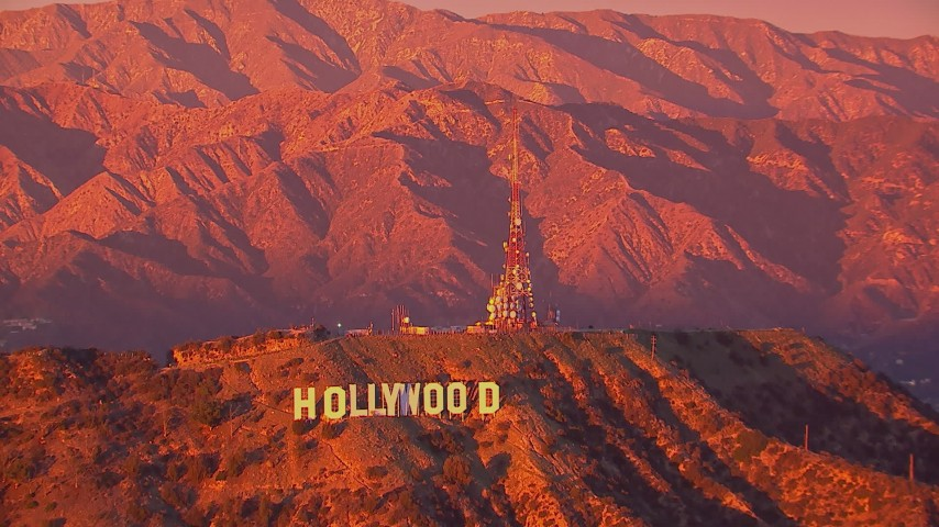 HD stock footage aerial video of flying away from the famous Hollywood Sign and radio towers at sunset, California Aerial Stock Footage | CAP_018_086