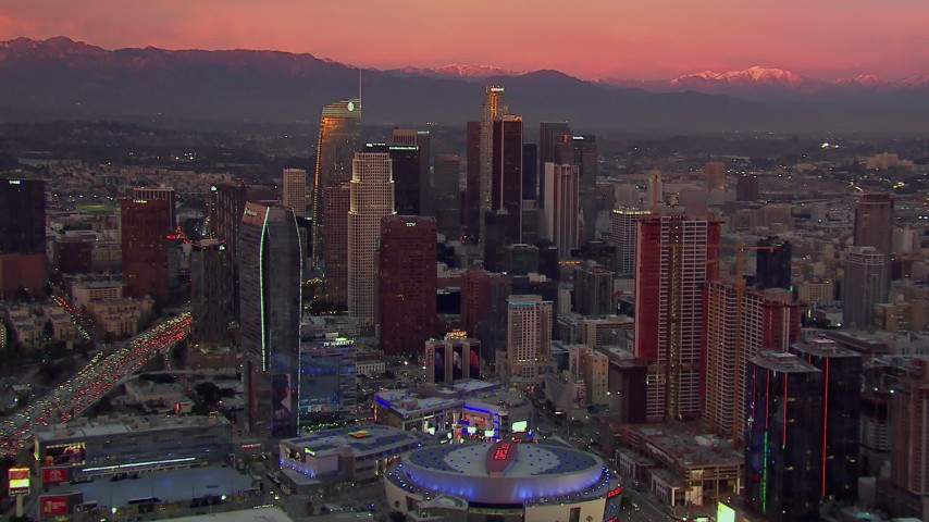 HD stock footage aerial video flying away from towering Downtown Los Angeles skyscrapers, reveal arena at sunset, California Aerial Stock Footage | CAP_018_098