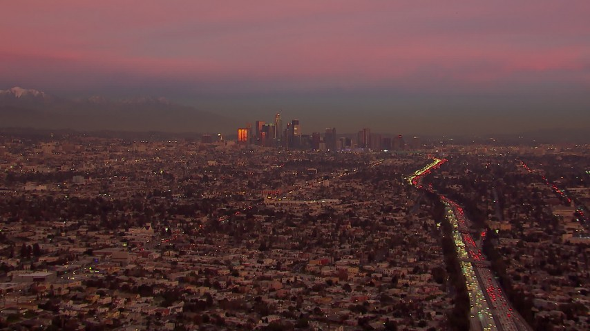 HD stock footage aerial video of a view of the distant Downtown Los Angeles skyline at sunset, California Aerial Stock Footage | CAP_018_105