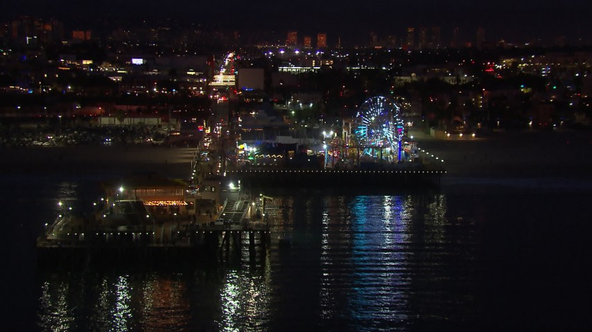 HD stock footage aerial video fly toward the Ferris wheel and rides at night, Santa Monica Pier, California Aerial Stock Footage | CAP_018_115