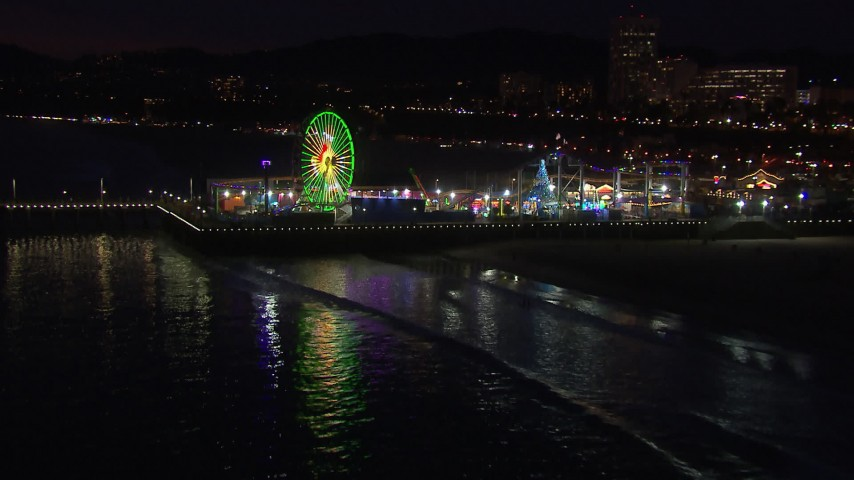 HD stock footage aerial video approach the Ferris wheel and rides at nighttime from the ocean, Santa Monica Pier, California Aerial Stock Footage | CAP_018_119