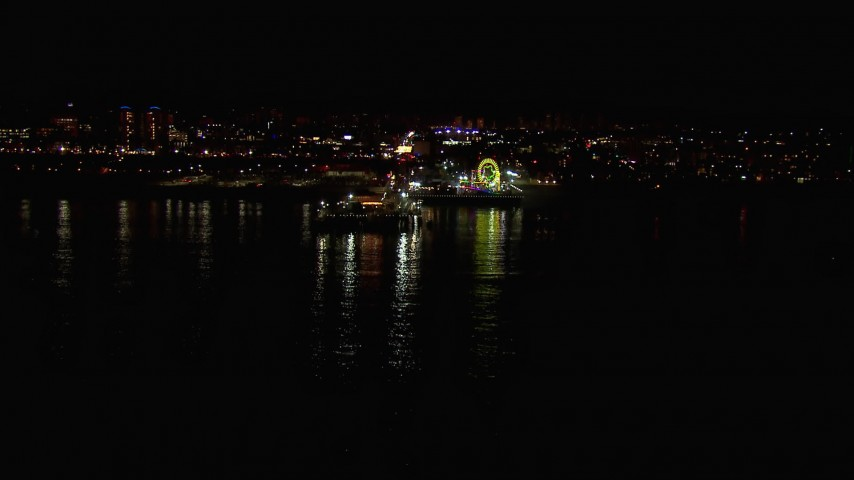 HD stock footage aerial video flying over the ocean toward the Ferris wheel and rides at nighttime, Santa Monica Pier, California Aerial Stock Footage | CAP_018_121