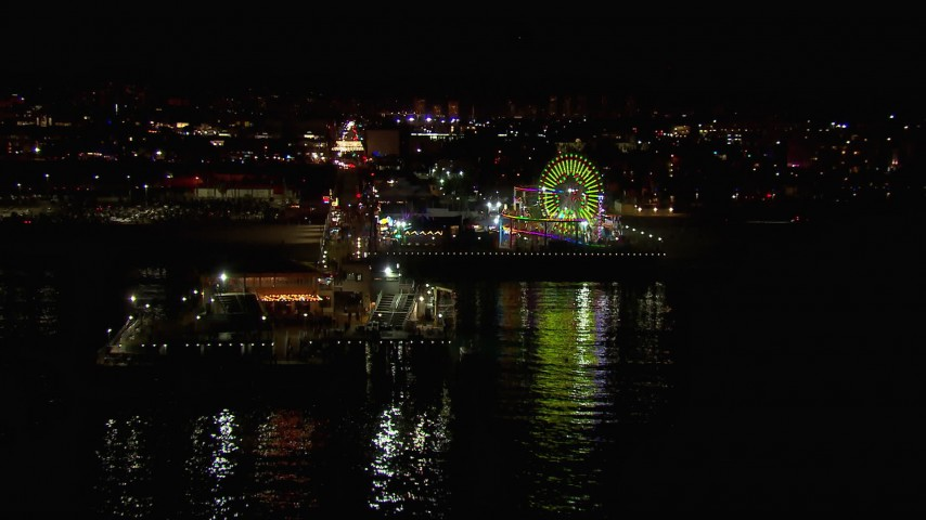 HD stock footage aerial video flying over the ocean to approach the Ferris wheel and rides at nighttime, Santa Monica Pier, California Aerial Stock Footage | CAP_018_122