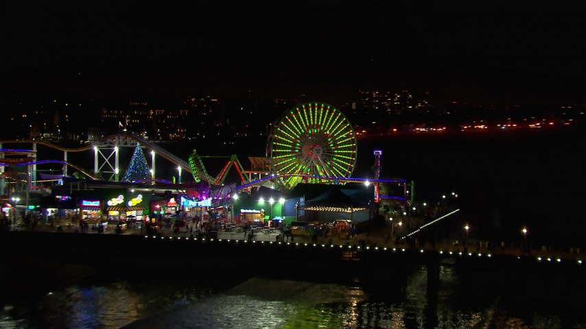 HD stock footage aerial video of a reverse view of the Ferris wheel and rides at nighttime, Santa Monica Pier, California Aerial Stock Footage   CAP_018_124
