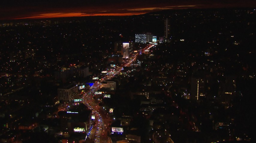HD stock footage aerial video tilt for a view of Sunset Strip billboards and traffic at night in West Hollywood, California Aerial Stock Footage | CAP_018_142