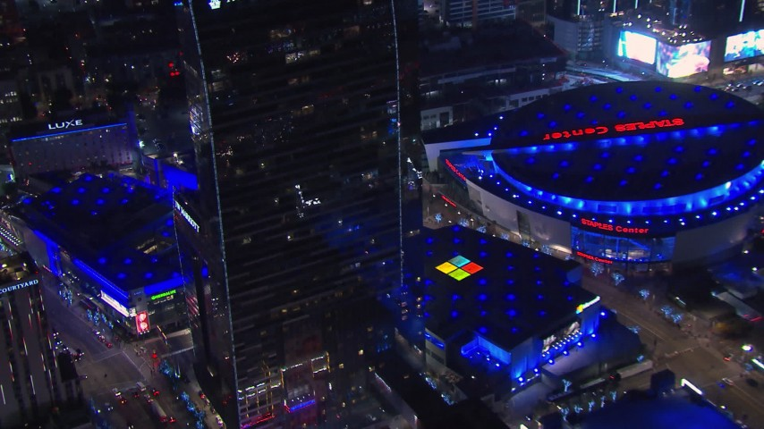 HD stock footage aerial video of flying by hotel and theater to reveal ice skating at night, Downtown Los Angeles, California Aerial Stock Footage | CAP_018_190