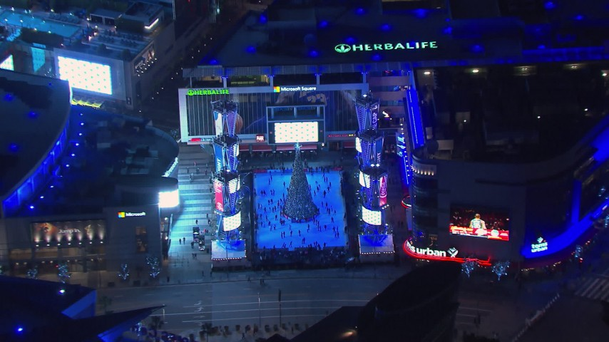 HD stock footage aerial video zoom to wider view of an ice skating rink and Christmas tree at night, Downtown Los Angeles, California Aerial Stock Footage | CAP_018_193