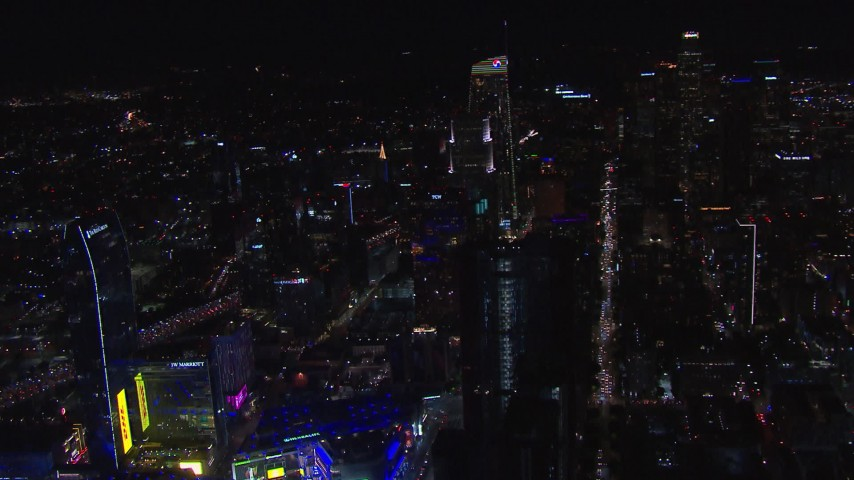 HD stock footage aerial video orbit hotel under construction at night, reveal Downtown Los Angeles skyline, California Aerial Stock Footage | CAP_018_198