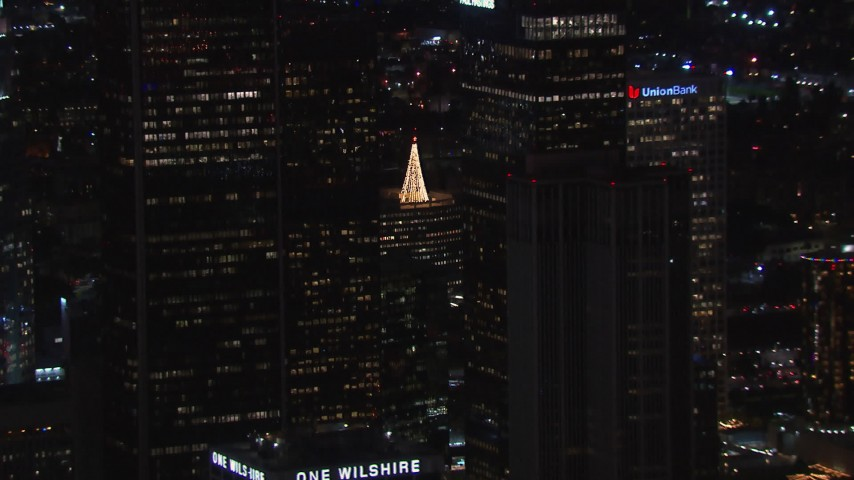 HD stock footage aerial video of flying by skyscrapers at night to reveal holiday decorations, Downtown Los Angeles, California Aerial Stock Footage | CAP_018_212