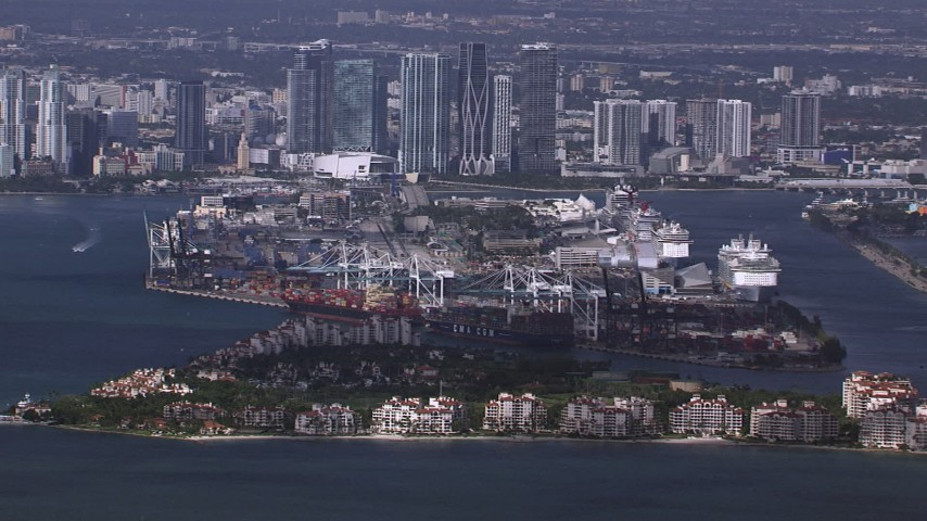 HD stock footage aerial video of passing Fisher Island, Port of Miami and downtown skyline, Florida Aerial Stock Footage | CAP_020_026
