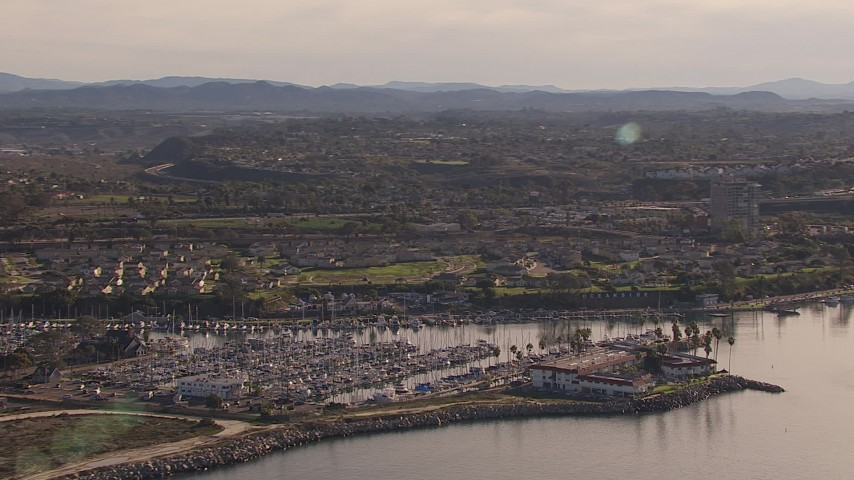 HD stock footage aerial video of a marina and oceanfront hotel by coastal neighborhood, Oceanside, California Aerial Stock Footage | CAP_021_027