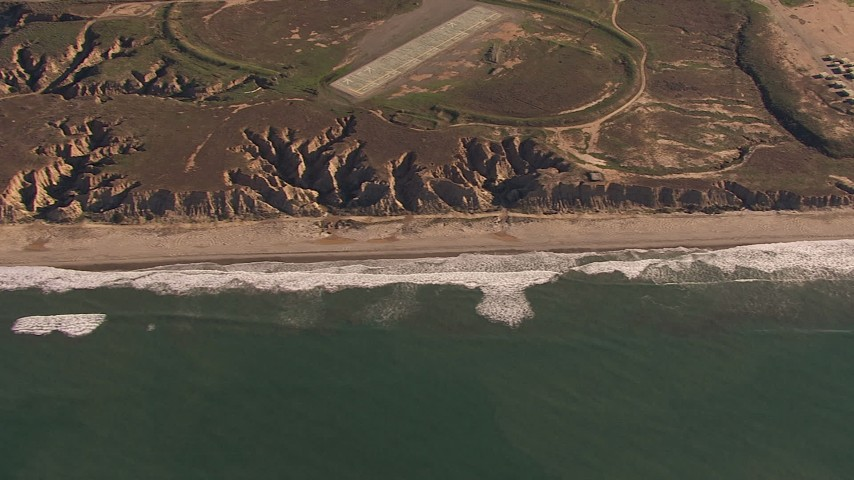 HD stock footage aerial video of passing by an empty strip of beach as waves roll toward the coast, Oceanside, California Aerial Stock Footage   CAP_021_039
