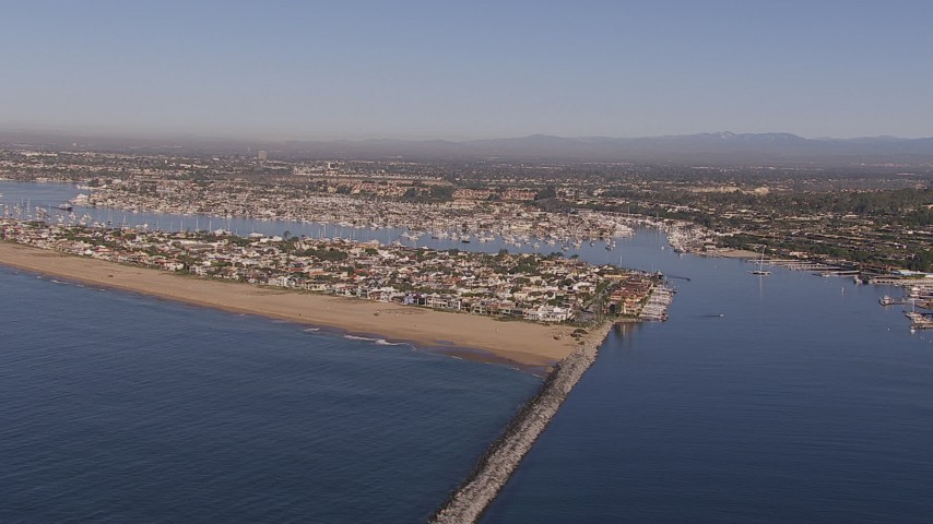 HD stock footage aerial video of passing by the inlet to the bay by coastal neighborhoods, Newport Beach, California Aerial Stock Footage | CAP_021_075