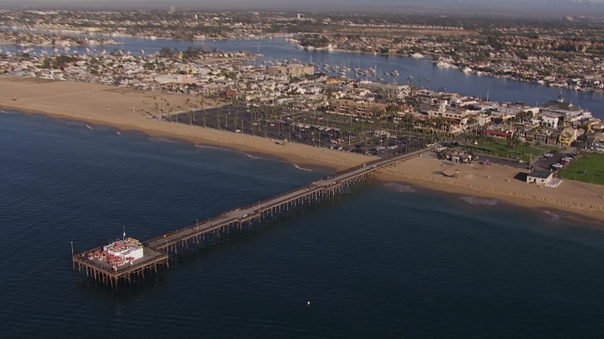 HD stock footage aerial video approach and orbit pier by the beach and coastal neighborhoods, Newport Beach, California Aerial Stock Footage | CAP_021_077