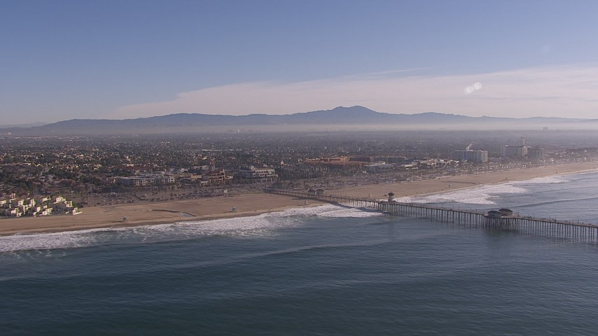 HD stock footage aerial video of flying by a pier and the beach in Huntington Beach, California Aerial Stock Footage | CAP_021_083