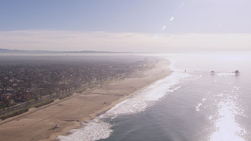 HD stock footage aerial video of flying away from a pier and the beach in Huntington Beach, California Aerial Stock Footage | CAP_021_084
