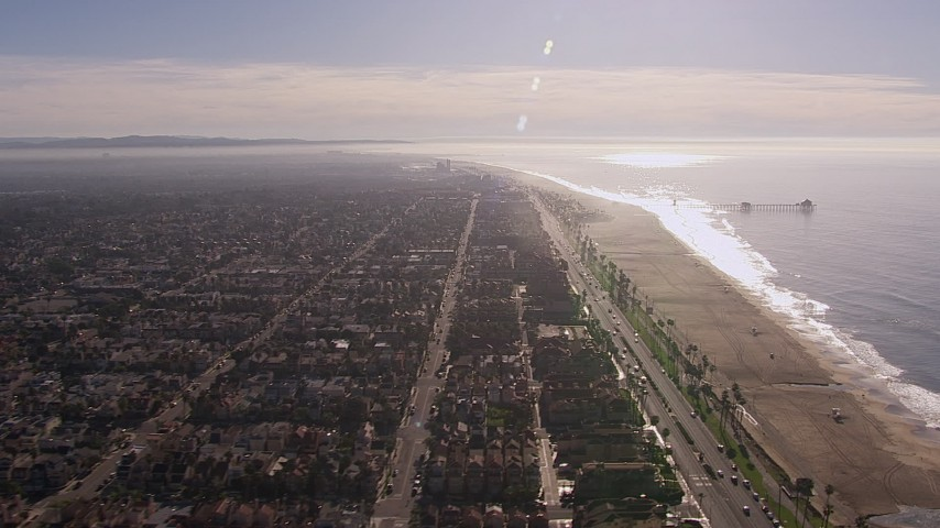 HD stock footage aerial video of a reverse view of a pier and the beach in Huntington Beach, California Aerial Stock Footage | CAP_021_085