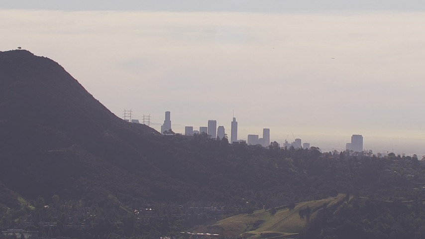 HD stock footage aerial video of the city's skyline on a hazy day, eclipsed by the Hollywood Hills, Downtown Los Angeles, California Aerial Stock Footage | CAP_021_130
