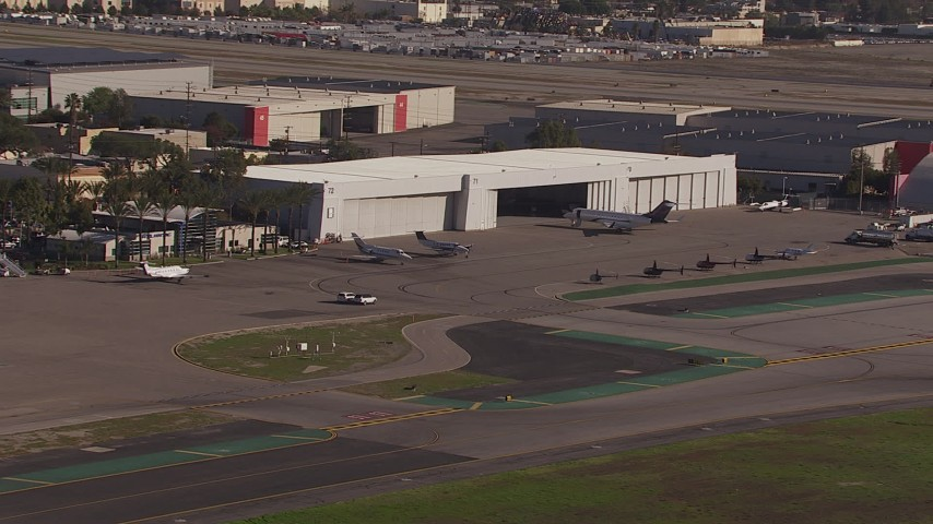 HD stock footage aerial video of civilian jets and helicopters at a Burbank Airport hangar, California Aerial Stock Footage | CAP_021_132