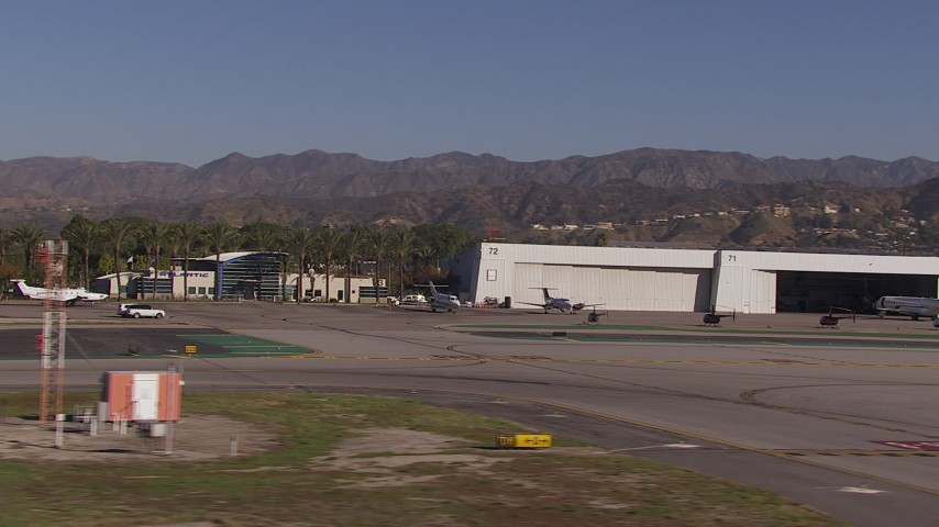 HD stock footage aerial video of civilian jets and helicopters by aviation building and a Burbank Airport hangar, California Aerial Stock Footage | CAP_021_134