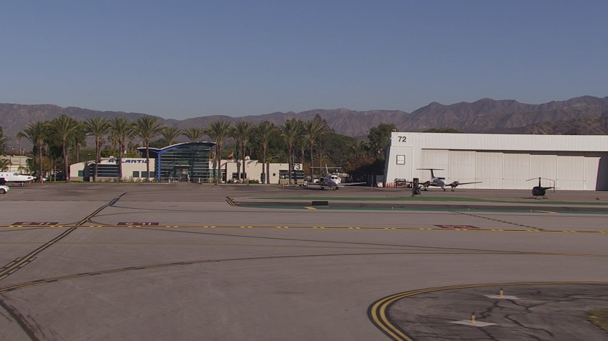 HD stock footage aerial video approach civilian jets by aviation building at Burbank Airport, California Aerial Stock Footage | CAP_021_135