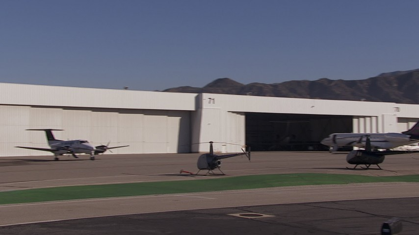 HD stock footage aerial video of passing civilian jets and helicopters by a Burbank Airport hangar, California Aerial Stock Footage | CAP_021_136
