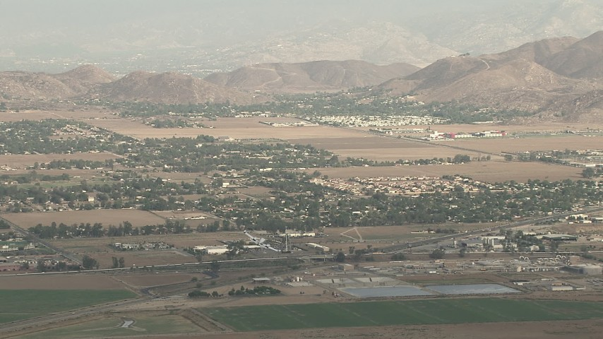 HD stock footage aerial video of tracking Cessna 340 banking over farmland on hazy day, Perris, California Aerial Stock Footage | CBAX01_004