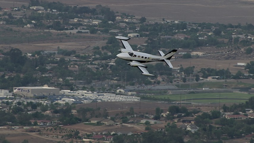 HD stock footage aerial video of tracking Cessna 340 entering frame, flying over rural town, Perris, California Aerial Stock Footage | CBAX01_020