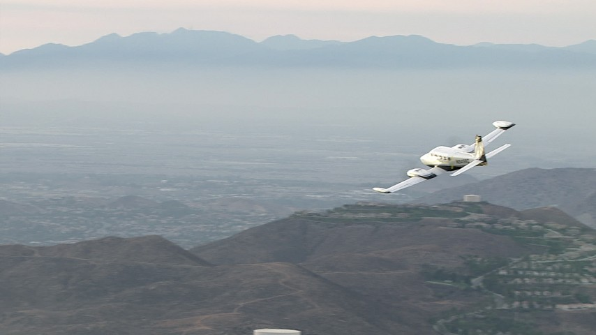 HD stock footage aerial video of flying by hazy hills, revealing Cessna 340, Perris, California Aerial Stock Footage | CBAX01_025