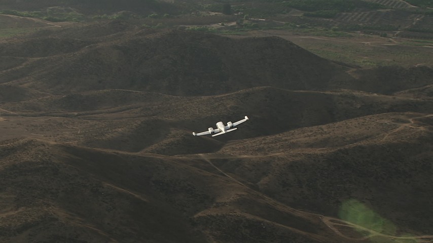 HD stock footage aerial video of tracking Cessna 340 over hills then out of frame on hazy day, Perris, California Aerial Stock Footage | CBAX01_028