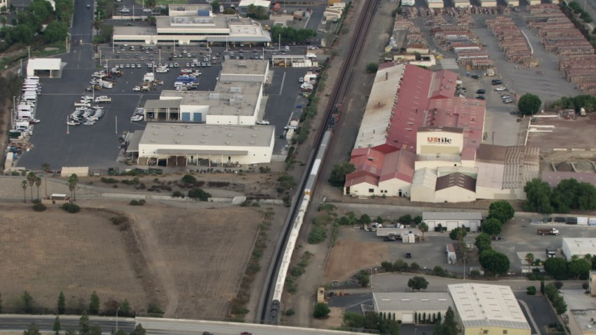 HD stock footage aerial video of tracking train through commercial area, Corona, California  Aerial Stock Footage | CBAX01_034