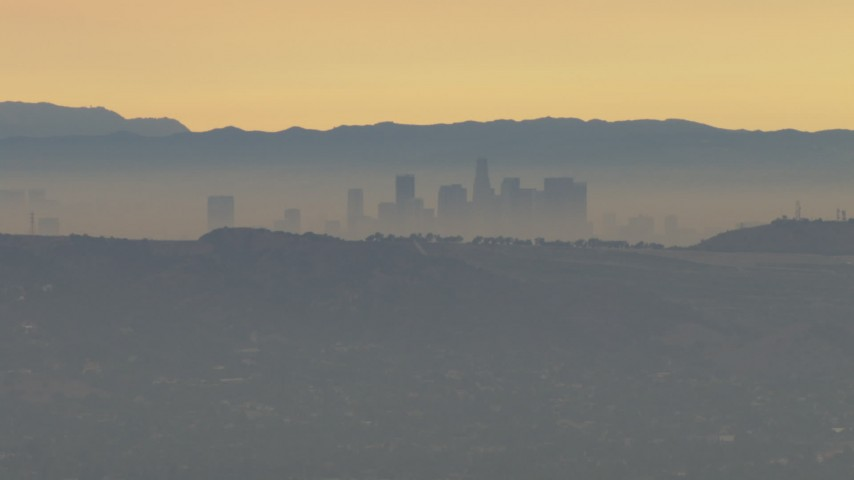 HD aerial video fly by smoggy skyline beyond hills, Downtown Los Angeles, California, sunset Aerial Stock Footage | CBAX01_059