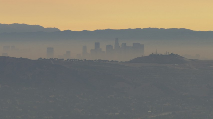 HD stock footage aerial video of fly by smoggy skyline beyond hills, Downtown Los Angeles, California, sunset Aerial Stock Footage | CBAX01_061