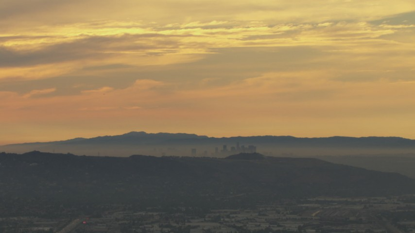 HD stock footage aerial video of a smoggy skyline beyond hills, Downtown Los Angeles, California, sunset Aerial Stock Footage | CBAX01_062