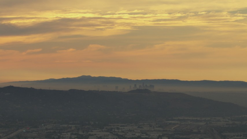 HD aerial video of a smoggy skyline beyond hills, Downtown Los Angeles, California, sunset Aerial Stock Footage | CBAX01_063