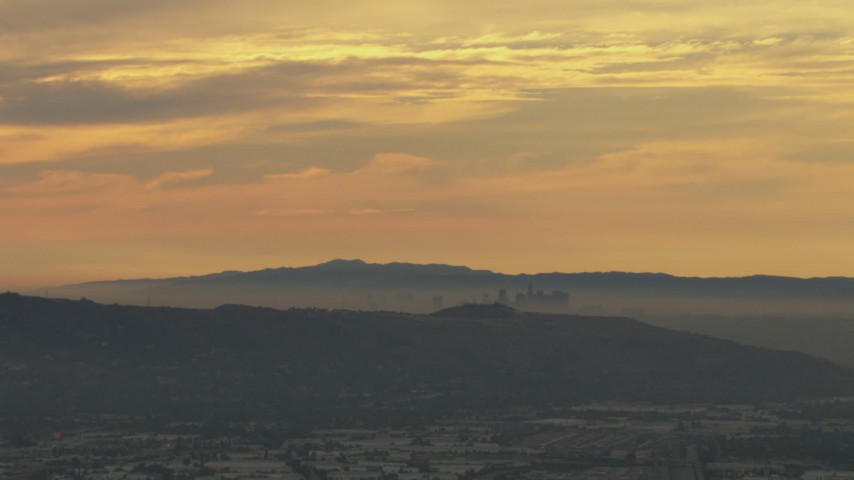 HD stock footage aerial video of smoggy skyline beyond hills, Downtown Los Angeles, California, sunset Aerial Stock Footage | CBAX01_064