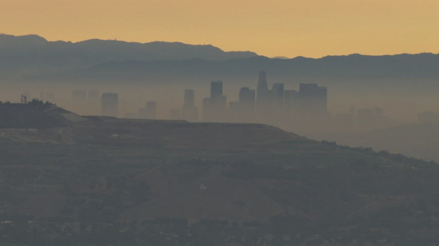 HD aerial stock footage video of the smoggy skyline beyond hills, Downtown Los Angeles, California, sunset Aerial Stock Footage | CBAX01_066